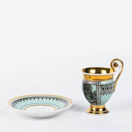A CUP AND SAUCER IN PARTLY GILT VIENNESE PORCELAIN WITH A LIGHT GREEN UNDERTONE. WORK FROM THE FIRST