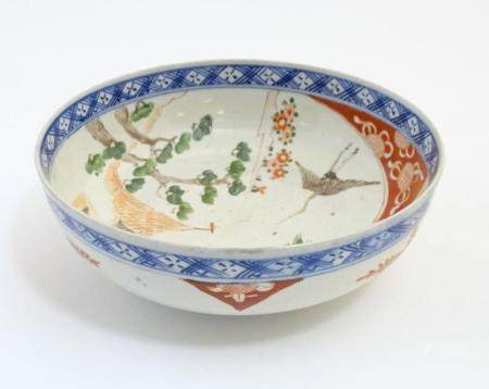 A Japanese bowl with hand painted decoration depicting a landscape scene with flowers, a crane bird