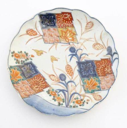 A Japanese plate with a lobed rim, hand painted in the Imari palette with stylised flowers and birds