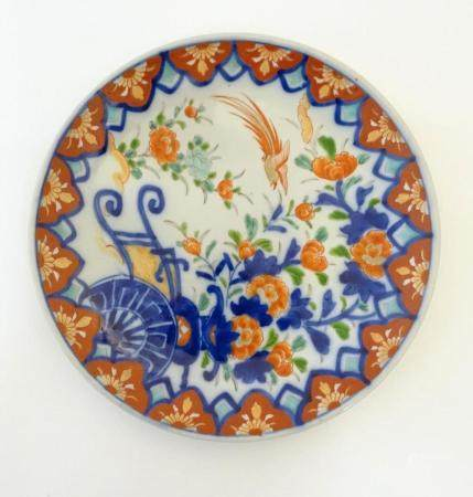 An Oriental plate in the Imari palette decorated with flowers, foliage and an Asiatic pheasant. Impr
