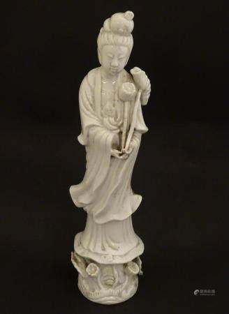 A Chinese blanc de chine figure of Guanyin holding flowers, raised on a base of lotus flowers and li