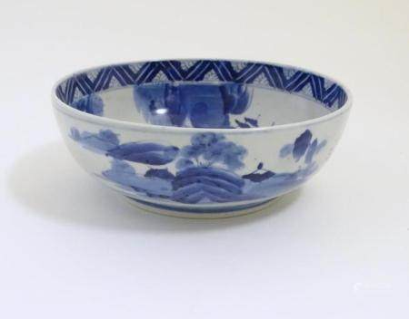 A Chinese blue and white bowl with hand painted decoration depicting an Oriental landscape with pago