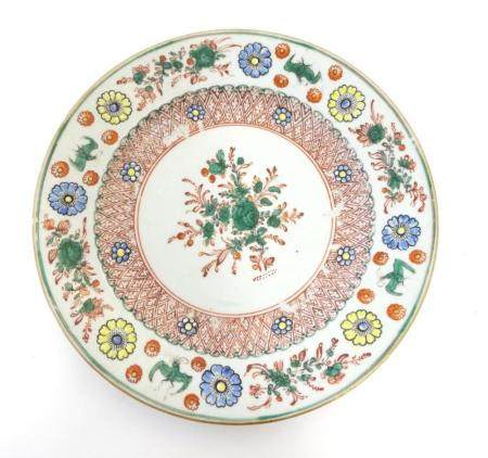 A Chinese plate with central floral and foliate detail, with a patterned border with flowers and sty