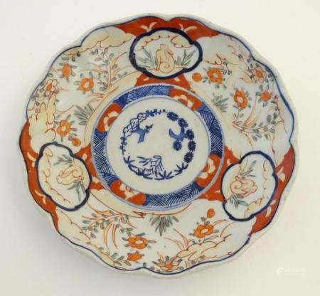 An Imari style plate with a lobed rim, decorated with floral and foliate scenes with panelled depict