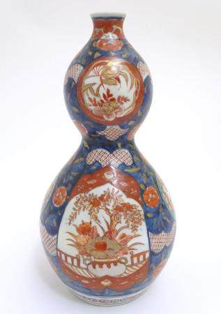 An Oriental double gourd vase in the Imari palette with lobed panels depicting plants on a terrace,