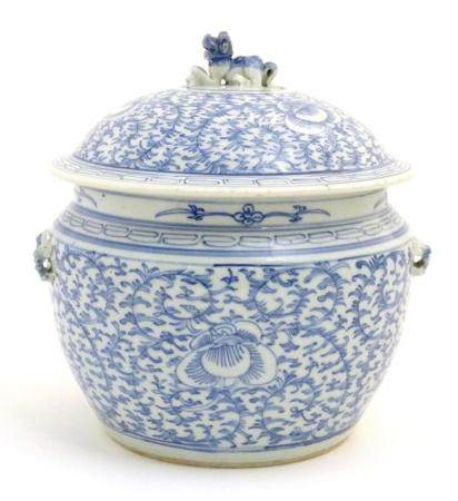 A Chinese blue and white pot and cover with scrolling floral and foliate detail. The lid surmounted