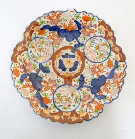 A Japanese Imari plate with a scalloped rim with stylised leaf veins in relief to the centre, decora
