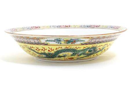A Chinese famille jeune bowl decorated with two dragons and patterned border. Character marks under.