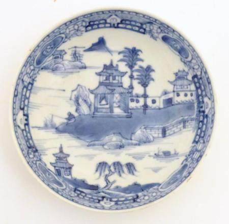 A Chinese blue and white dish / bowl with hand painted decoration depicting a landscape with trees,