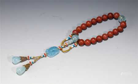A CHINESE CARVED RED HARDSTONE PRAYER BEADS