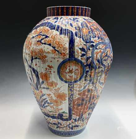 A large Japanese Imari floor standing porcelain vase, Meiji Period, the ribbed body and white ground
