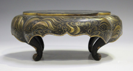 A Japanese lacquer stand, Meiji period, of lobed oblong form, the apron decorated with gilt waves on