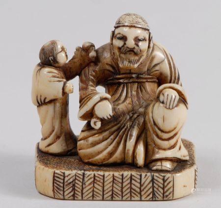 Lot de deux netsuke-okimono en ivoire, l'un représentant un enfant et une sorcière portant un m