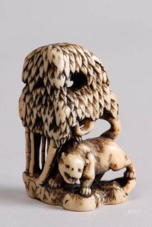 Deux netsuke en ivoire rehaussé de brun représentant un tigre auprès d'un pin; et un enfant as