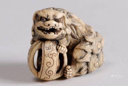 Deux netsuke en ivoire teinté, l'un représentant un shishi avec une balle; l'autre, figurant u