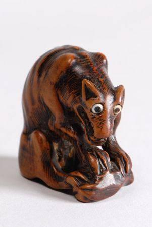Deux netsuke en bois, l'un représentant un loup assis, une cuisse de cervidé entre les pattes,