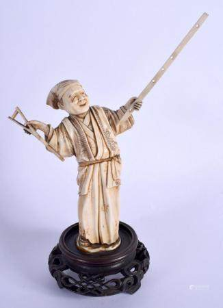 A 19TH CENTURY JAPANESE MEIJI PERIOD CARVED IVORY OKIMONO modelled holding a long stick. Ivory 16.5 cm high.