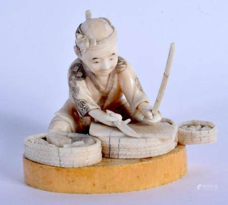 A 19TH CENTURY JAPANESE MEIJI PERIOD CARVED IVORY FIGURE OF A MALE modelled preparing fish. 8 cm x 9 cm.