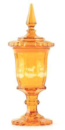A 19TH CENTURY BOHEMIAN AMBER GLASS VASE AND COVER the faceted top with a tapered finial on matching