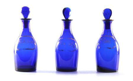 A SET OF THREE EARLY 19TH CENTURY BRISTOL BLUE GLASS DECANTERS for Rum, Brandy and Hollands with