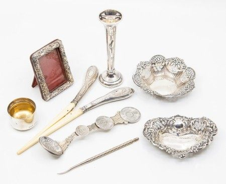 A collection of silver items to include two pin dishes, small bud vase, a small silver frame with