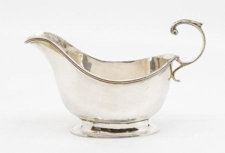 A silver sauce boat, embossed foliate C scrolled handle, Birmingham 1938, Adie Brothers Ltd
