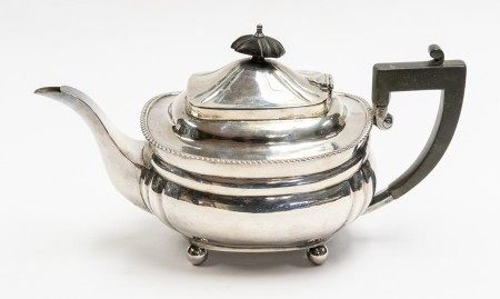 A Georgian style silver teapot, ebonised final and handle, on four ball feet, by Elkington & Co.,