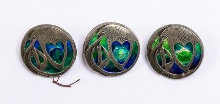 Liberty & Co: A set of three Art Nouveau Cymric silver circular buttons, cast in low relief with