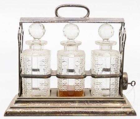 An Edwardian silver-plated three bottle tantalus, by Walker and Hall, with key