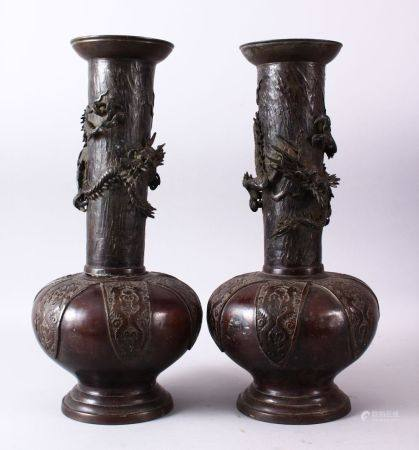 A PAIR OF 18TH CENTURY JAPANESE BRONZE VASES, bulbous shaped and tapering tops with dragons in