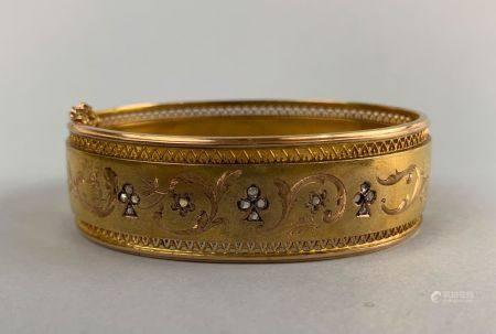 Bracelet articulé en or jaune 750 millièmes à décor ciselé et gravé de volutes feuillagées, de