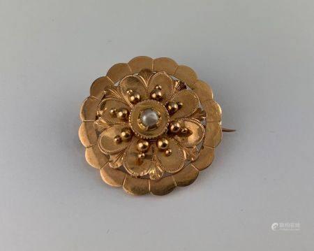 Broche ronde en or rose (750 millièmes) figurant une fleur stylisée sertie d'une demie perle de