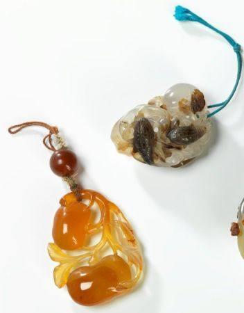Deux pendentifs en agate Chine, début du XXème siècle Le premier à décor ajouré de fruits et in
