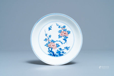 A Chinese blue, white and copper red saucer dish with floral design, Kangxi