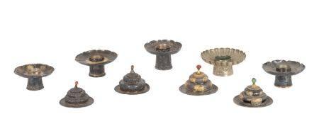Tibet, XIXe siècleLot de quatre couvercles et cinq bougeoirs en métal (probablement en argent)