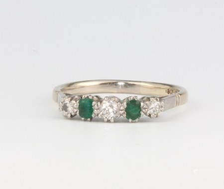 An 18ct white gold emerald and diamond ring, the 3 brilliant cut diamonds approx. 0.17ct, the 2 oval