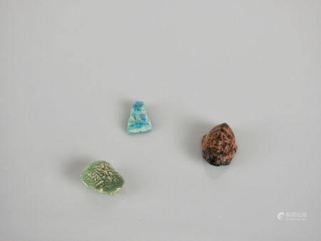 Trois amulettes antiques : Deux visages et un buste d'Isis .Pâte de verre et pierre. En l'état.