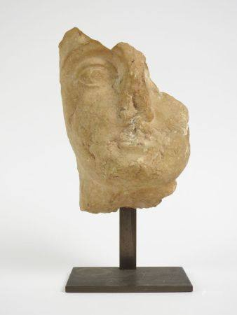 Fragment de tête de divinité probablement le Dieu Amon.Marbre ou calcaire patiné.Basse Epoque.