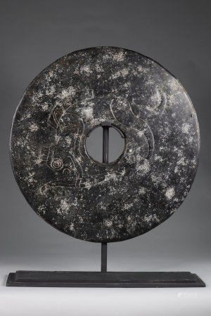 China Giant Bi-Disc, in black jade, decorated, in relief, with a fanciful animal, with human features ... Anthropomorphic