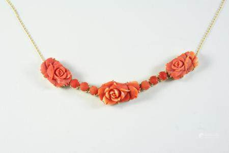 A CARVED CORAL NECKLET formed with three carved coral flowerheads and six coral cabochons, in