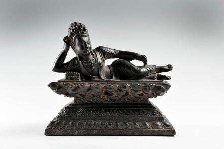 A CAST-IRON FIGURE OF A RECLINING GUANYIN