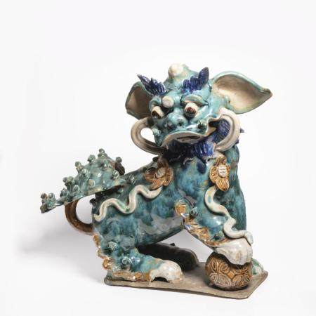 A GREEN, AUBERGINE AND YELLOW GLAZED POTTERY ROOF TILE FIGURE OF A FU LION