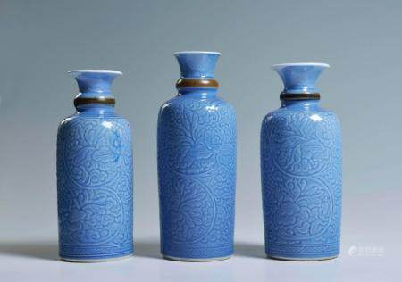 A GROUP OF THREE FINELY CARVED BLUE-GLAZED BOTTLE VASES