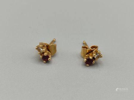 Paire de clous d'oreilles en or jaune? ornés d'un brillant et d'une pierre rouge. Non poinçonné