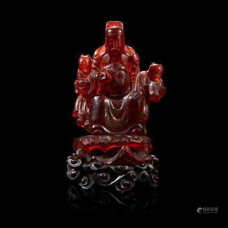 A Chinese carved amber figure of a sage and acolytes,