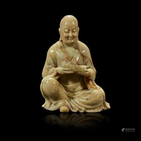 A finely-carved Chinese soapstone figure of a seated luohan,