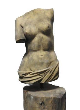 Corps féminin acéphale bras manquants le torse nu vêtu d'un drapé tombant sur ses hanches dans