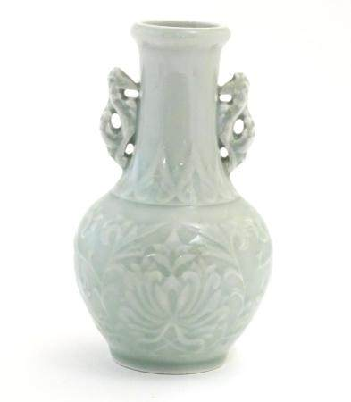 A Chinese celadon green baluster vase with twin handles and stylised foliate design. Approx. 6 1/