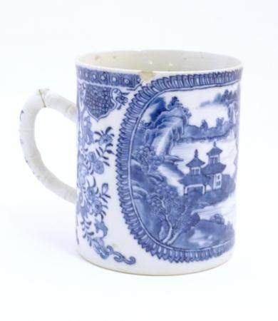 A Chinese blue and white export mug depicting a landscape scene with pagodas, with floral and