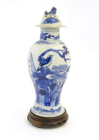 A Chinese blue and white vase and cover with floral, foliate and bird detail. The lid with foo dog